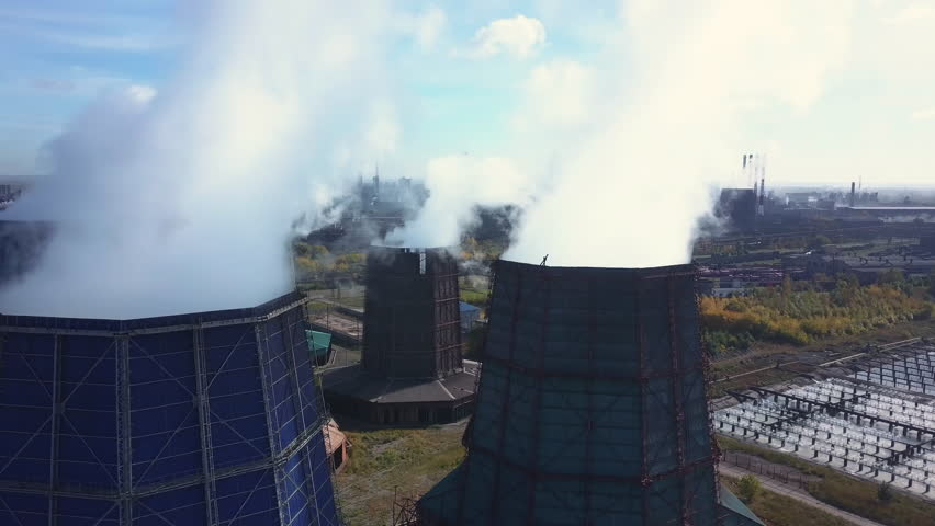 Drone extremely near flight between several steel plant tubes through the clouds of smoke, industrial park landscape with autumn trees and plants, air emissions from manufacturing sector, Chelyabinsk