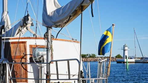 Swedish flag blowing in the wind on a vintage sailing boat. Lighthouse in the background. Location lake Vattern in Granna, Sweden.