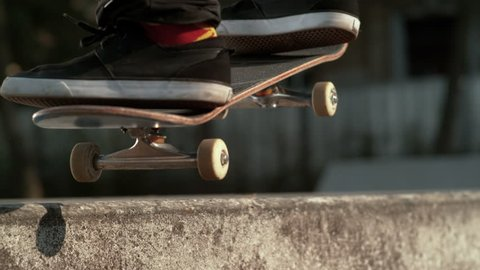 SLOW MOTION, MACRO, DOF: Unrecognizable man with colorful cannabis socks skateboarding in the outdoor park grinds a concrete ledge. Cinematic shot of young athlete doing a cool skateboarding trick.