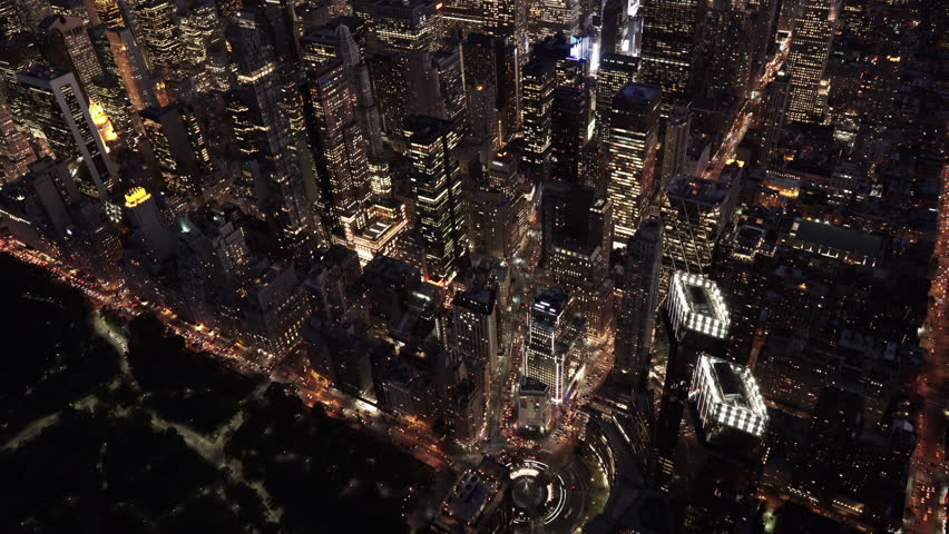 New York City Circa-2015, aerial shot at night tilting down from a view of Midtown and Downtown Manhattan, revealing Columbus Circle and Central Park from above