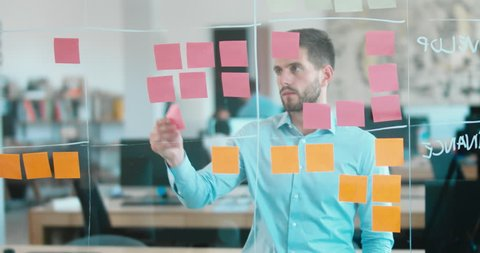 Caucasian male worker standing near glass wall with sticky notes, framework for managing work, scrum methodology. 4K UHD 60 FPS SLOW MOTION