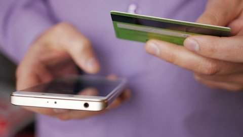 Businessman in a purple shirt making online payment with credit card and smartphone, online shopping, lifestyle technology. Man enters the bank card number into the smart phone. Closeup. Close up.