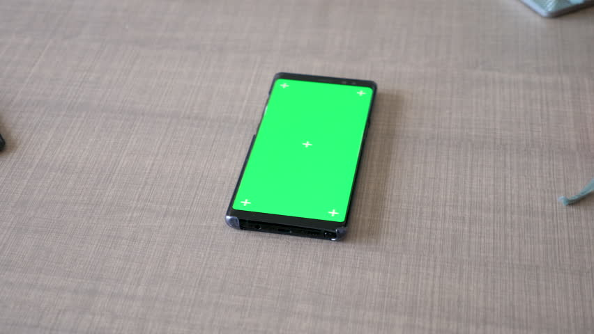Modern smartphone with green screen chroma mock up lying on the desk. Dolly slider 4K footage | Shutterstock HD Video #1017038362