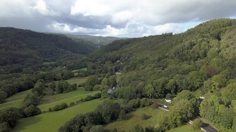 Aerial track forward over woodland and dense forests in 4K