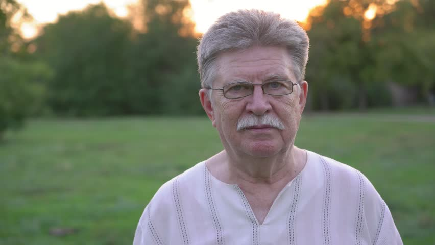 old positive man takes off his glasses in the park,4k 3 #1017084172