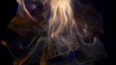 Argentinian 500 and 1000 pesos bills burning to disappear
