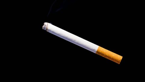 Smoking causes sexual impotence.  Timelapse video of a burning cigarette against  black background