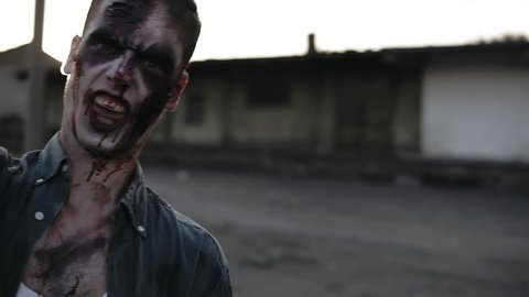 Portrait of a male zombie with bloody teeth and wounded face screaming and shouting. Halloween, filming, staging concept. Blurred abandoned town on the background