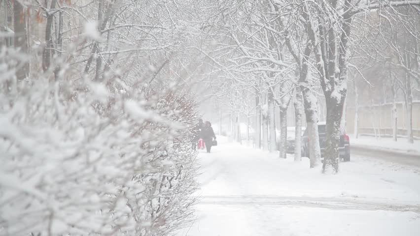 Children are walking along a snow-covered street. people walk along snow-covered streets. The snowfall paralyzed traffic in the city. pedestrians in winter on a white snow-swept street during the day