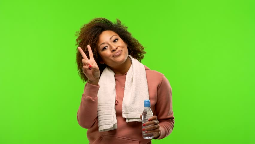Young afro american fitness woman on a green chroma screen fun and happy, positive and natural, doing a gesture of victory, peace concept