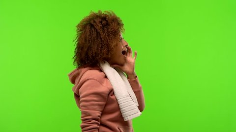 Young afro american fitness woman on a green chroma screen whispering gossip undertone, trying not to be heard