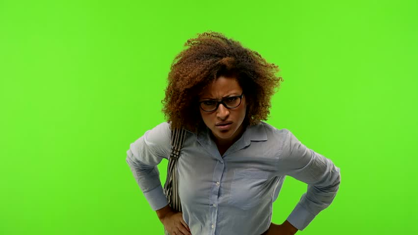 Young afro american student woman on a green chroma screen looking forward, scolding someone very angry