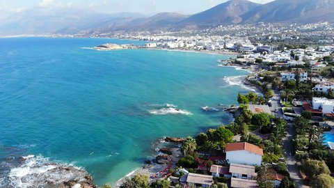Fly over Crete seafront and Hersonissos town. Panorama from top on beach and waves