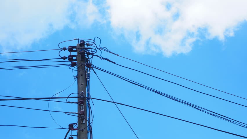 Timelapse of electricity pole standing in clouds and blue sky background.