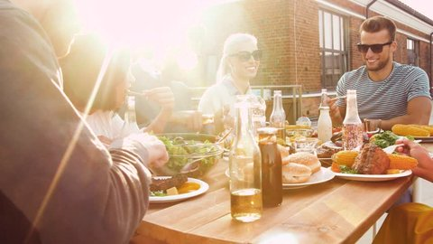 leisure and people concept - happy friends having dinner or bbq party and eating on rooftop in summer