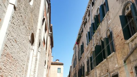 VENICE, ITALY - JULY 7, 2018: beautiful old architecture of Venice, a house with old green shutters and flowers on the windowsills, against the blue sky, on a hot summer day,