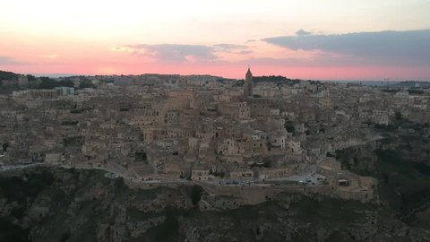Aerial view of Matera, Basilicata, Italy. Sunset light with violet sky and sun going down on the Sassi of Matera, Unesco heritage.