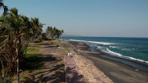 4K aerial drone flying footage of young couple on the wild black sand beach. Bali island.