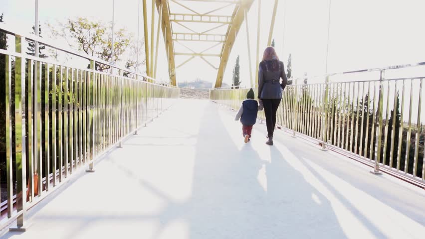 Mom and little son go over the bridge | Shutterstock HD Video #1017276682