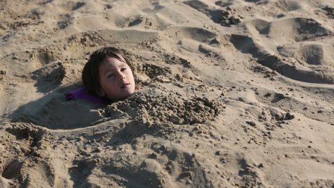 Little boy, child, buried in the sand, body under sand, head out, smiling happily