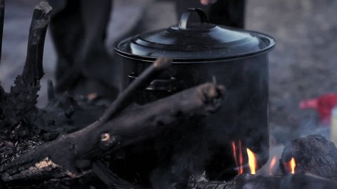 Yukon river, Yukon Territory, Alaska. Night camp of a canoe expedition to Alaska. Hand with wooden spoon stirs the boliling water in a pot on a camp fire.