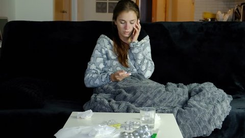 Slow motion of young sick woman with fever talking on the cell phone with her doctor and taking pills.