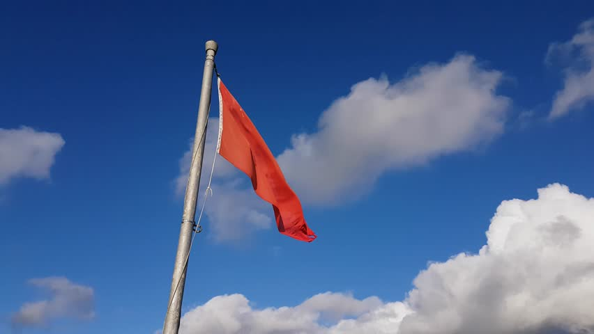 Close up of a red flag blowing in the wind with blue sky and clouds in the background. | Shutterstock HD Video #1017340222