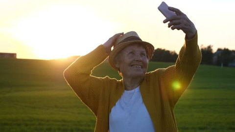 Hip Grandma Taking Selfie In Straw Hat With Smartphone At Sunset