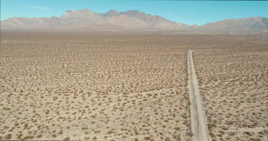 AERIAL - A drone flies over a big piece of desert filled with tumbleweed with in the distance a few mountains on a blue and sunny day | Shutterstock HD Video #1017388552