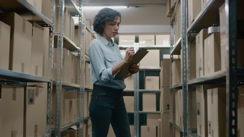 Female Inventory Manager Checks Stock, Writing in the Clipboard. Beautiful Woman Working in a Warehouse Storeroom with Rows of Shelves Full Of Cardboard Boxes, Parcels, Packages Ready for Shipment. | Shutterstock HD Video #1017422692