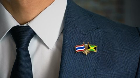 Businessman Walking Towards Camera With Friend Country Flags Pin Thailand - Jamaica