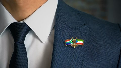 Businessman Walking Towards Camera With Friend Country Flags Pin South Africa - Equatorial Guinea