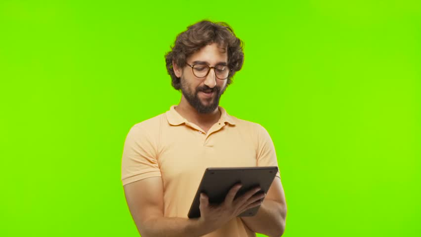 Young bearded silly man using a tablet against chroma key editable background. ready to cut out the person. | Shutterstock HD Video #1017440002