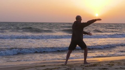 Athletic man pushing hands while practicing wushu on beach in the morning