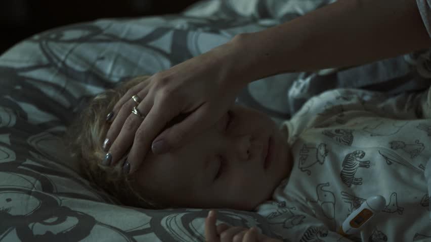 Late night shot. Mother taking care of her sleepy sick little boy. | Shutterstock HD Video #1017479572