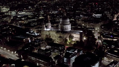 Aerial Night View of St. Paul's Cathedral in London. 4K Birds Eye View Video feat. Religious Iconic Church and Tourism Landmark with traffic on London city streets and orbiting Monument in England, UK