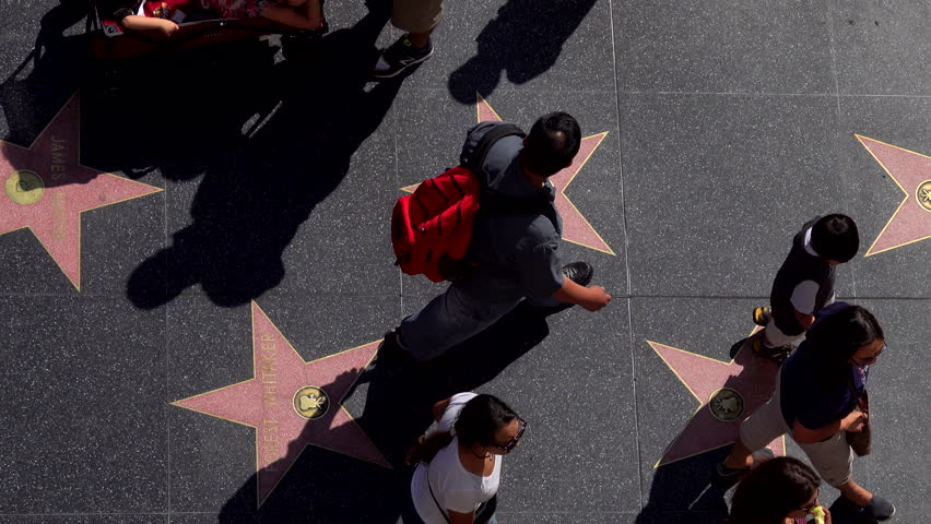 Los Angeles, CA / USA - Sept. 29, 2018 - Pedestrians walk across the iconic, pink stars lining the Walk of Fame in Hollywood on a late afternoon day, as viewed from overhead. | Shutterstock HD Video #1017525292