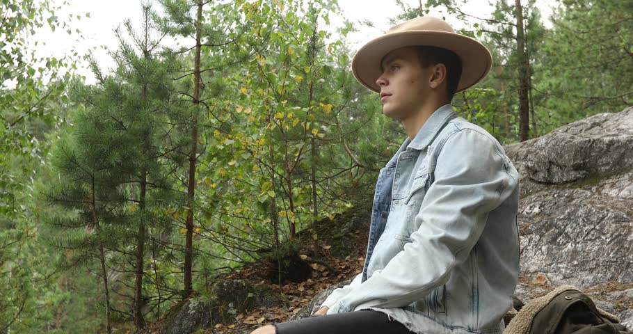 Young handsome man in jeans and warm jacket sitting on rocky cliff in forest on background of green trees #1017533242