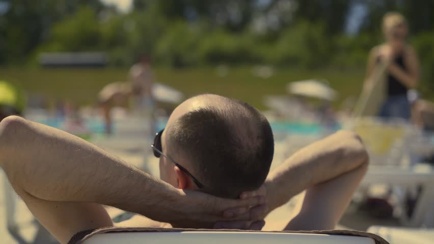 Back view, Close-up: Bald Italian man is lying on the beach, on a sun lounger, sunbathing. Wearing sunglasses, he puts his hands under his head. He looks at the girls passing by.