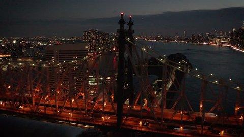 dusk orbiting Queensboro Bridge from river to NYC