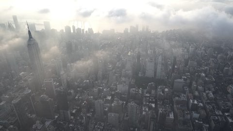 New York City Circa-2015, aerial view flying over the Flatiron District in Manhattan, facing the East River, with low level clouds and thick fog at sunrise