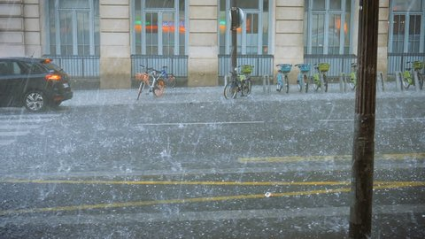 Extreme weather hail rain storm on the streets of Paris hail beats bicycles