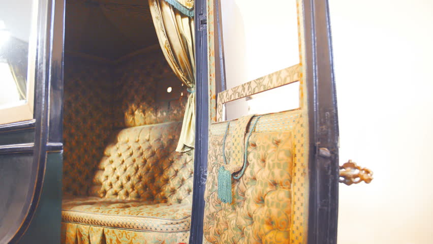 Rich women retro horse carriage inside details 4K. Dolly slide shot zoom-in of inside the vintage carriage in focus. Beautiful design of the seat.
