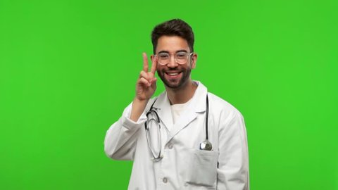 Young doctor man on green chroma fun and happy, positive and natural, doing a gesture of victory, peace concept