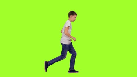 Teenage boy in white t-shirt and jeans running on green chroma key background, Side view, 4k pre-keyed footage