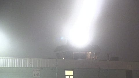 Markham, Ontario, Canada October 2018 Air traffic control tower beacon flashing at airport in heavy fog at night