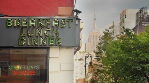 A daytime exterior establishing shot of a city corner diner's neon sign in midtown Manhattan.