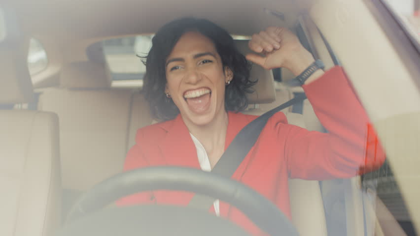 Portrait of Beautiful Woman Driving Car, Has Fun, Listens to Music and Dances. Camera Shot Made From the Front Windshield.
