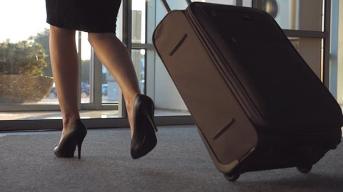 Business lady leaving airport through automatic glass door with her luggage. Young woman in heels walking from terminal and roll suitcase on wheels. Concept of work trip or travel. Slow motion