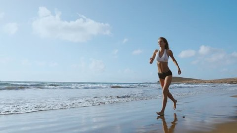 f86aa838dc Healthy woman running on the beach, girl doing sport outdoor, happy female  exercising,
